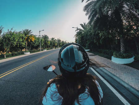 A girl in a black helmet is driving a motorcycle on a flat road in China. Traveler rides next to palm trees, trees grow along the road.