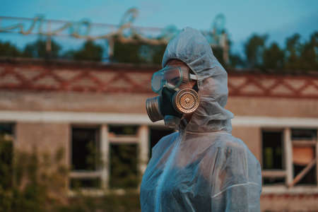The scientist put on a respirator and a white protective suit against radiation. Close-up profile of a girl who cares about ecology.