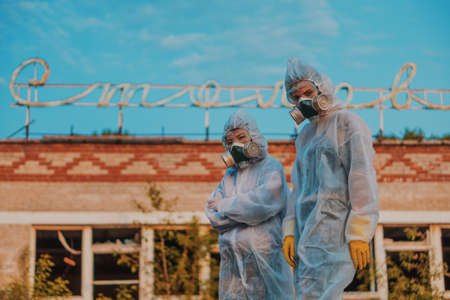 Two scientists put on a respirator and a radiation protective suit. Stern look into the camera from the abandoned territory. Care about ecology in bright saturated photos.