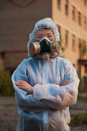 A scientist in a white protective suit of Asian appearance cares about ecology. Respirator on a girl in an abandoned area.