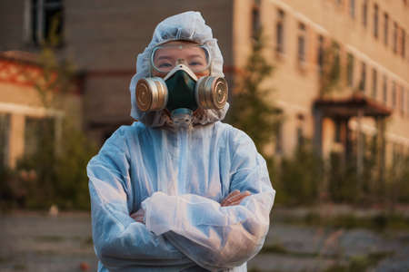 A scientist in a white protective suit of Asian appearance cares about ecology. Respirator on a girl in an abandoned area. 写真素材
