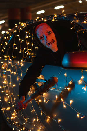 A man in a mask looks out of a car window in a parking lot at night. The killer is holding a baseball bat. Scary costume from the Purge for Halloween. The car is decorated with a New Years garland. 写真素材