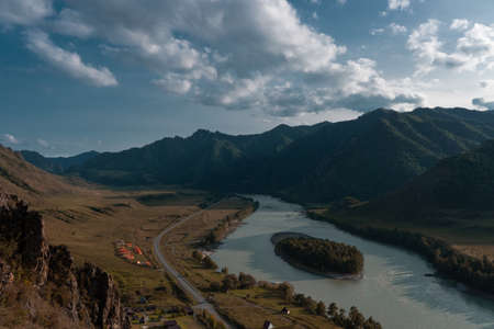 Beautiful landscape of forest mountains and flowing river. The Great Altai Mountains are the best place for recreation and tourism. Blue sky with clouds on a summer day.