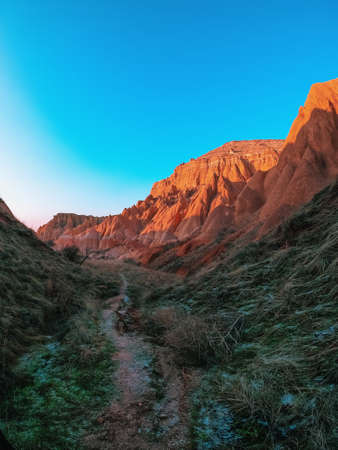 Trail at the foot of the Red Mountains in Turkey. Frosty morning in the Red Valley in Cappadocia. The green grass is covered with frost.