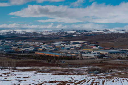 Panorama of an industrial plant in the mountains in winter. Working materials containers are located in the middle of natural surroundings. 写真素材 - 163554614