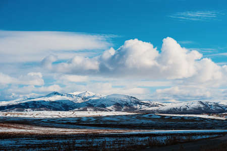 Panorama of a beautiful landscape with high mountains in winter. Field, road and forest near the snowy mountains in Turkey.