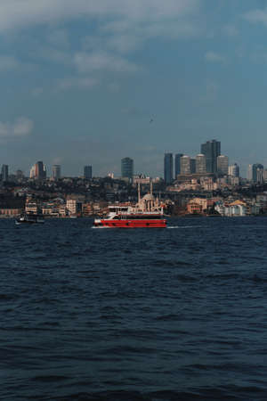A passenger red motor ship sails on the Bosphorus Gulf in Istanbul. 写真素材 - 163555863