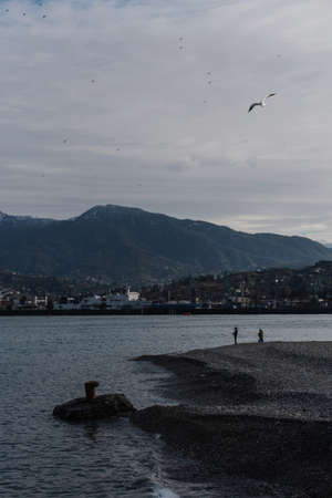 Two fishermen cast their fishing rods on the shore of a port in Batumi, Georgia. Beautiful landscape with high mountains, cloudy sky and blue river.