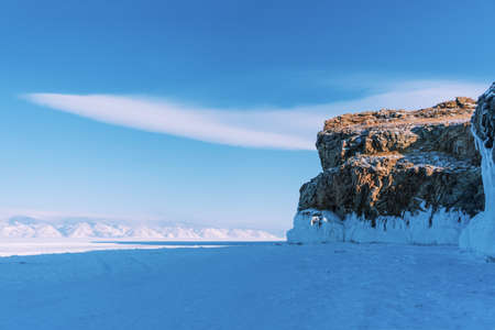 Lake Baikal in winter day. High cliffs on Olkhon Island. Large beautiful blocks of ice cover the foothills of the mountains.