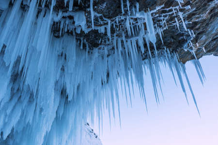 Amazing rock covered with ice. The frosty cave is covered with large icicles on Lake Baikal. 写真素材