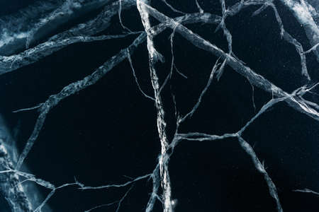 Ice on the Baikal lake. Beautiful cracked ice in winter close-up.