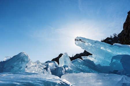 Splinters of broken ice on the Lake Baikal. A block of ice blocks the sun. Beautiful colored ice in Russia. 写真素材