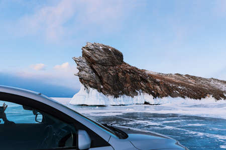 Ogoy island on Lake Baikal in winter. A gray car stands on clear ice against the backdrop of a beautiful rock. 写真素材