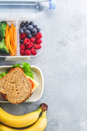 School lunch box with sandwich vegetables water almonds and fruits on grey table healthy