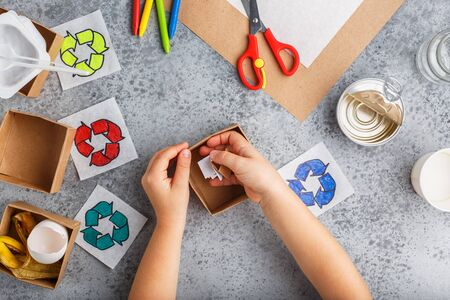Girl hands are making recycling game in paper on grey background colourful