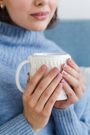 close-up of a girl in a blue sweater with a cup of hot tea in her hands