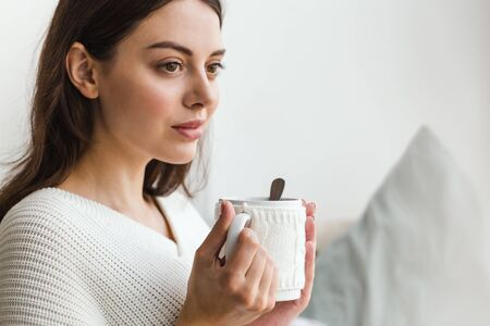 Beautiful face of a girl, a girl in white sweater sits on a sofa with a cup of hot tea in her hands