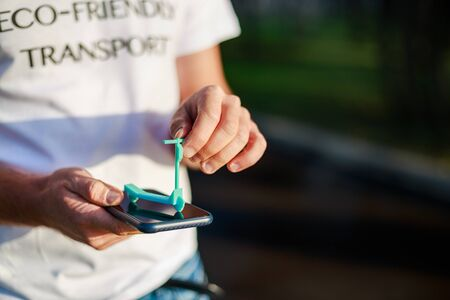 man hands is taking mini e-scooter over his smartphone t-shirt with text eco-friendly transport
