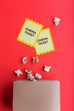 craft bag with popcorn and two yellow cinema tickets on red background flatlay