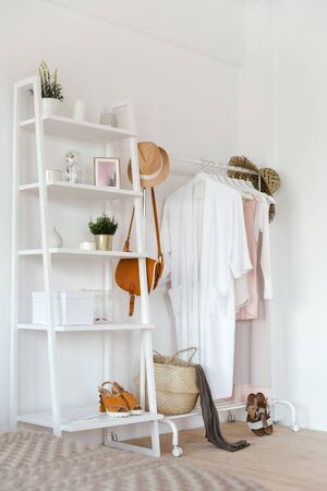 Hanger with clothes in trendy pastel colour on a rack with accessories in a cozy Scandinavian style
