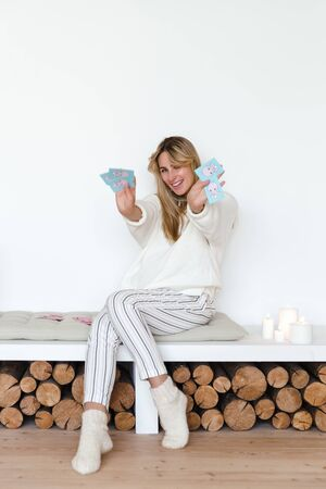 Girl in a white sweater and warm socks, sitting on a soft pillow in a Scandinavian style