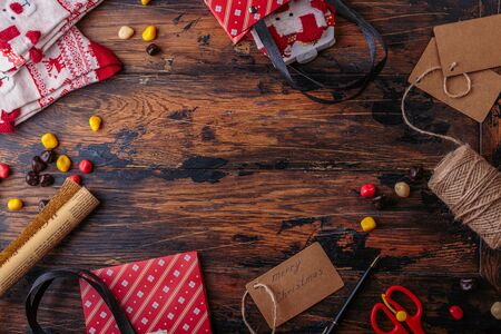 Gift boxes wrapped in red checked paper and the contents of a workspace composed. Flat lay. Valentines day, Christmas or New year gift packing. Holiday decor concept.
