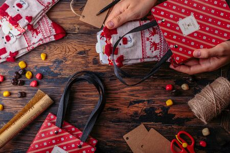 Christmas background. Top view of woman hands wrap New Year present and tie bow. Packed gifts and scrolls, spruce branches and tools on shabby wooden table.