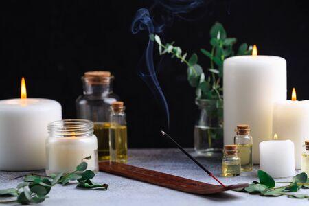 Räucherstäbchen mit Rauch auf Stein mit weißen Kerzen und ätherischen Ölen