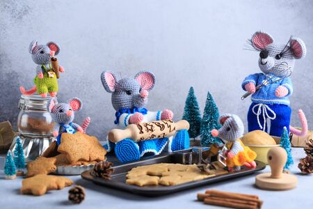 Knitted mouse family is cooking cookies. Year of rat. symbol of 2020.