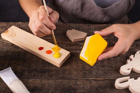 Woman creates a Christmas tree toy in her workshop. She paints the wooden blank neatly in yellow. Female hands without a face. Grey background. Symbol of the new year rat. 2020. View top