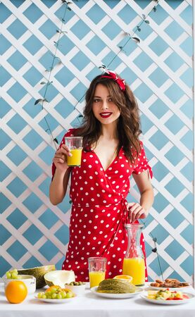 Pin-up girl in a red dress with a glass of orange juice in her hands
