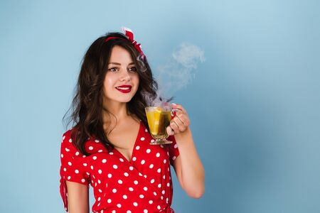 Pin-up girl in a dress stands on a blue background holding a cup with a drink