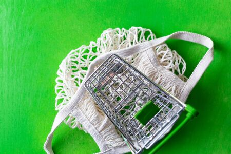 small shopping cart over mesh bag on green