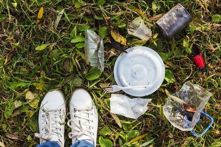 On the green grass are plastic items a plate, a bottle, cutlery, a broken bottle and a chewing can. Nearby are white man's sneakers. Concept - a man in harmony with nature. Say no to the trash. Stock Photo