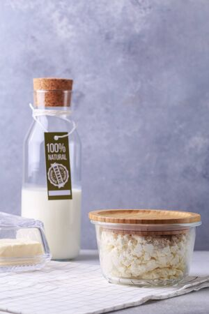 dairy products concept on grey bottle of milk with label natural products cottage cheese and butter
