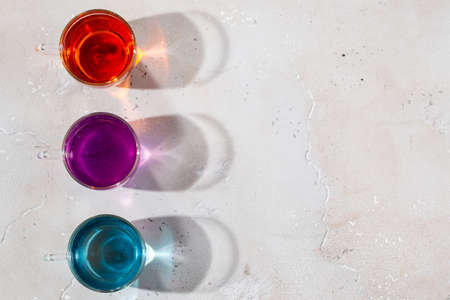 Glasses with colored liquid on a light marble background