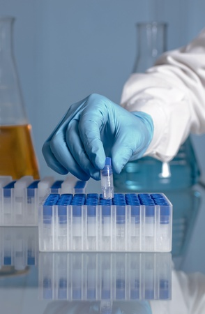 Hand of a lab technician taking a microtube of a rack with a flask in the background photo