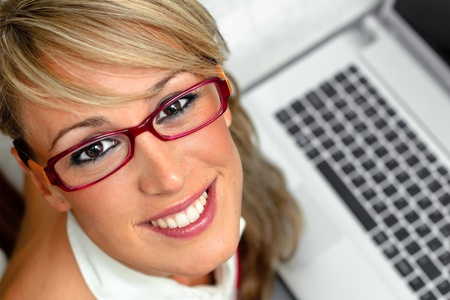 computer model: Attractive young woman with glasses and smiling in front of a laptop