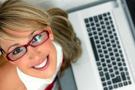 computer model: overhead shot of an attractive young female with glasses in front of a laptop