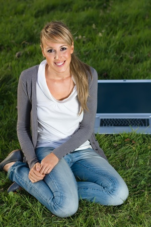 a beautiful smiling young woman sitting on grass next to a laptop on campus photo