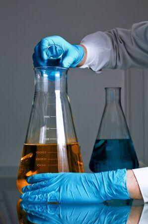 bureta: un científico de la mezcla de un pequeño frasco de líquido a un gran Foto de archivo