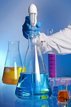 bureta: Escena en la que aparece el brazo de un técnico de laboratorio recogidos una dosis de líquido azul en un matraz con una pipeta digital. En el fondo son otras herramientas del laboratorio