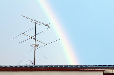 Old TV antenna on a roof with a rainbow in the background photo