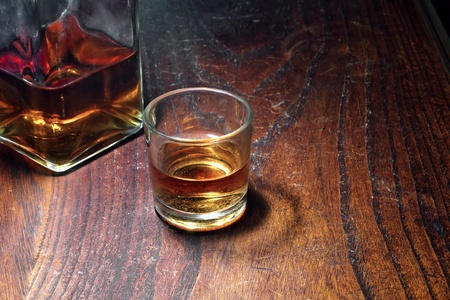 whiskey glass: A table with a glass and an old bottle of whiskey