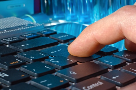 finger pressing the Enter key on a laptop with blue tubes in the background photo
