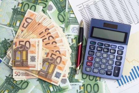 banconote euro: una calcolatrice, una penna e una relazione dei risultati su uno sfondo con le banconote