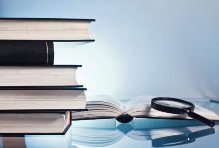 Un mucchio di libro attraverso la lente di ingrandimento whit