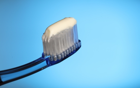 toiletries: toothbrush with toothpaste on a blue background