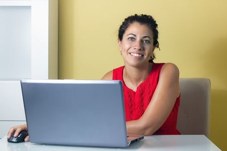e pretty: Woman sitting at home, working on a computer Stock Photo