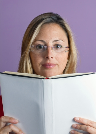 quietly: young woman reading a book quietly in a purple background